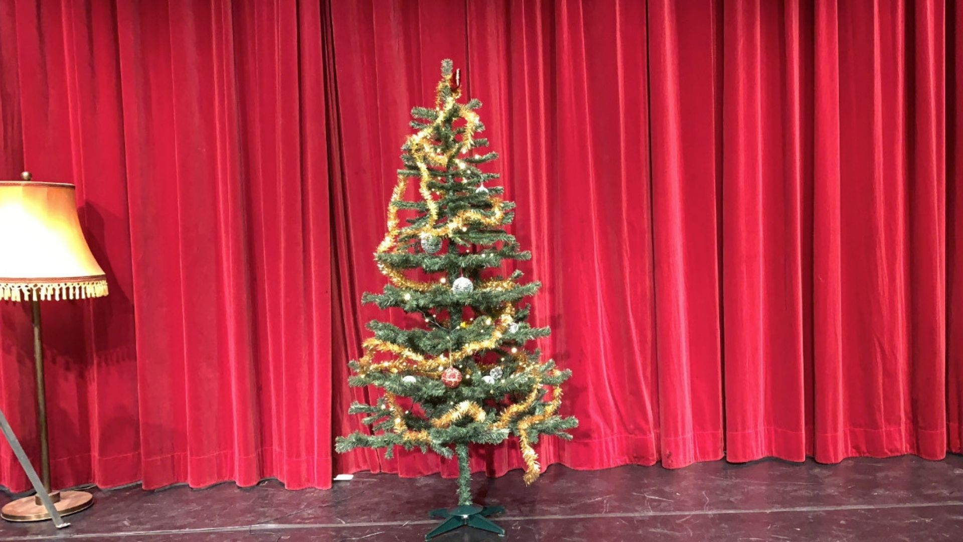 Bühne mit Weihnachtsbaum vor rotem Vorhang